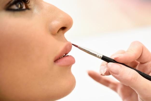 Maquilleuse maquillant les lèvres d'une jeune femme africaine