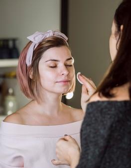 Maquilleuse nettoyant le visage du client