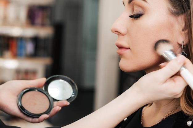 Maquilleuse avec un pinceau ombre à paupières maquillant le visage d'une femme