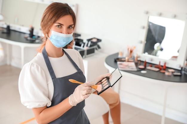 Maquilleuse portant un masque médical dans un salon pendant l'épidémie de coronavirus