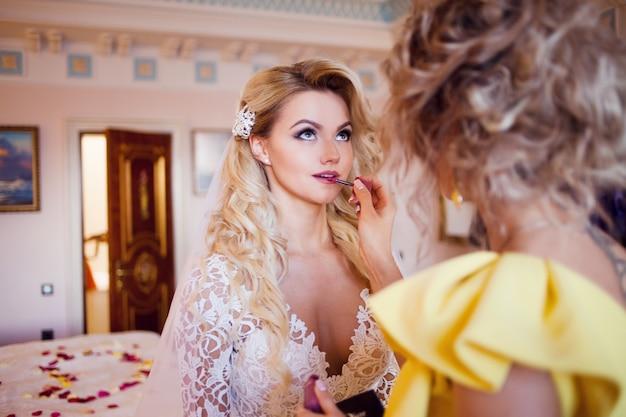 Maquilleuse prépare la mariée avant le mariage dans la matinée