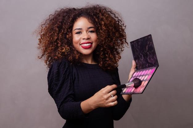 Maquilleuse professionnelle afro femme tenant des pinceaux de maquillage et une palette de fard à joues.
