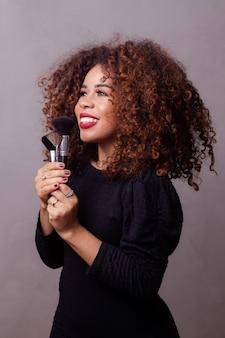 Maquilleuse professionnelle afro femme tenant des pinceaux de maquillage.