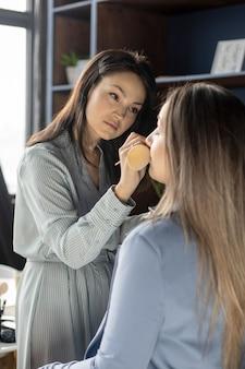 Maquilleuse professionnelle appliquant des cosmétiques sur le visage du modèle utilise une brosse travaillant au salon de beauté