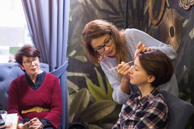 Maquilleuse professionnelle organise une master class pour améliorer les compétences d'un maquilleur débutant. concept de beauté et d'affaires.