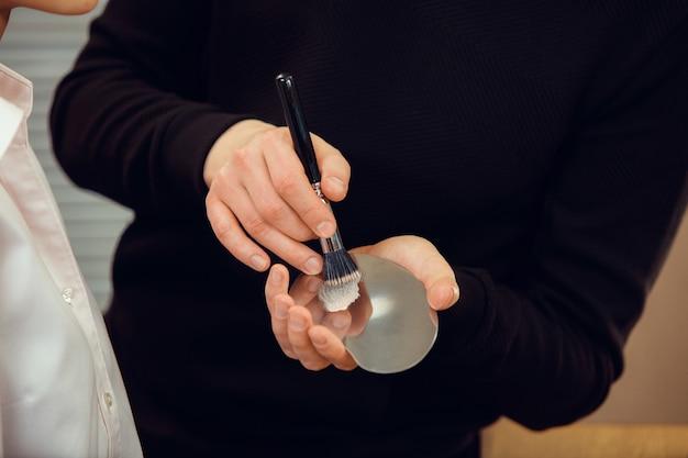 Maquilleuse professionnelle travaillant au salon. l'homme au proffesion féminine. concept d'égalité des sexes. mains mâles avec gros plan de brosse