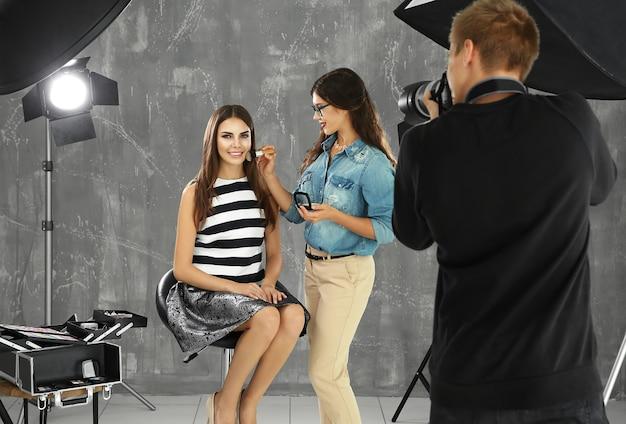 Maquilleuse professionnelle travaillant avec une belle jeune femme lors d'une séance photo