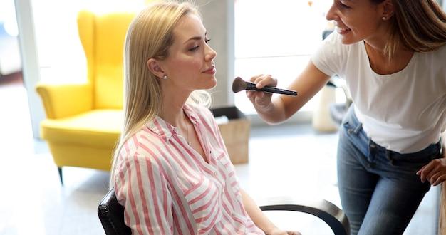 Maquilleuse travaille sur une belle femme blonde