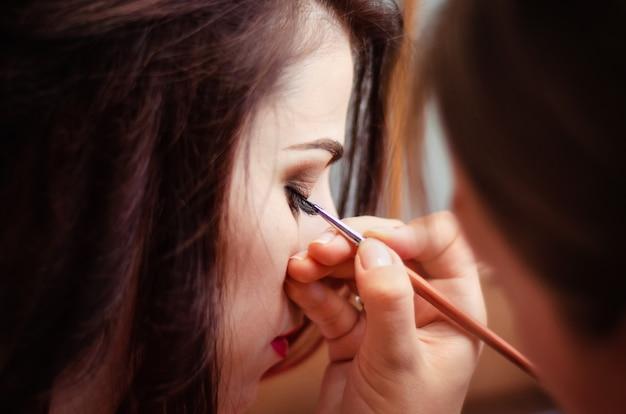 Maquilleuse travaille. maquilleuse maquillant les yeux de la mariée le jour du mariage.