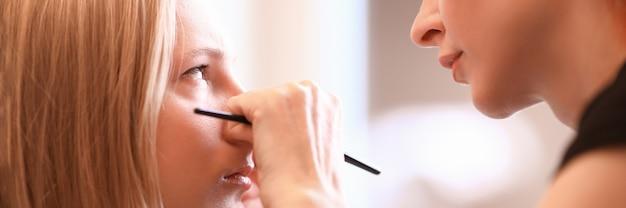 Maquilleuse travaille avec des yeux modèle féminin