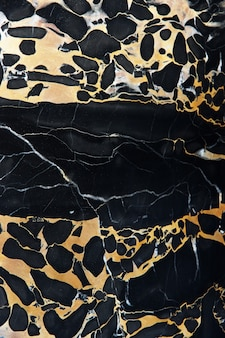 Marbre noir naturel poli avec des veines jaunes appelé nero portoro.