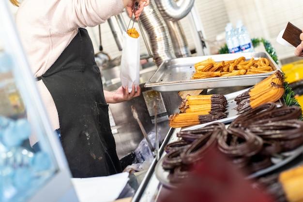 Marchand ambulant pâte frite, churros espagnols traditionnels au petit-déjeuner, baignés de chocolat.