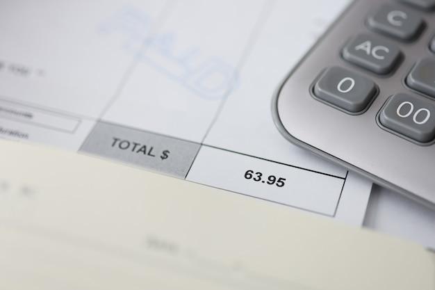 Marchandises payées et calculatrice sur papier de comptage pour les paiements basés sur le temps dans le bureau des finances des entreprises