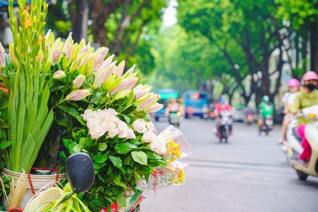 Marché aux fleurs et vélo sur la route dans le centre de hanoi vietnam composé de lilly.