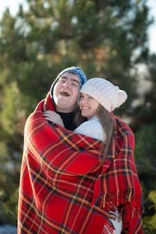 Marche d'hiver à travers les bois. le mec dans la couverture à carreaux rouge enveloppe la fille pour qu'elle ait chaud