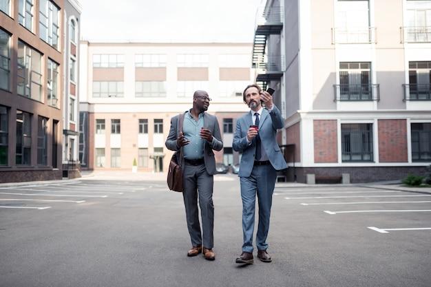 Marcher avec un collègue. homme d'affaires barbu aux cheveux gris marchant avec un collègue et buvant du café