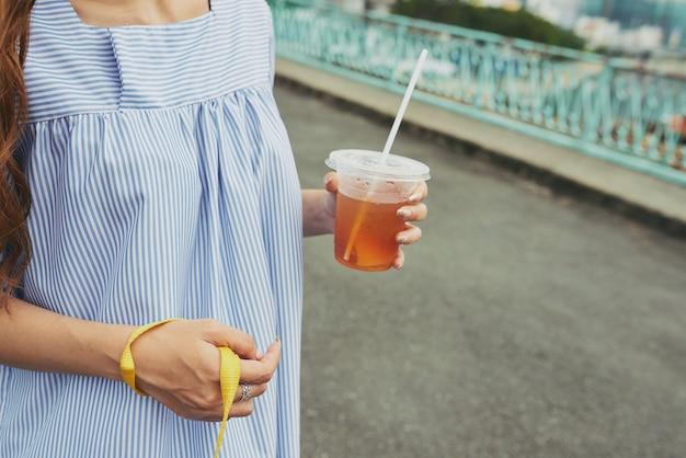 Marcher avec du thé glacé dans les mains