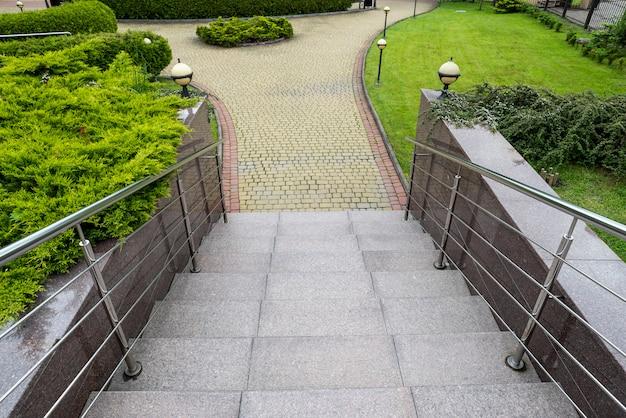 Marches de granit et de marbre dans un parc paysager avec garde-corps en chrome