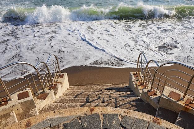 Marches en pierre descendant sur une plage de sable avec une promenade