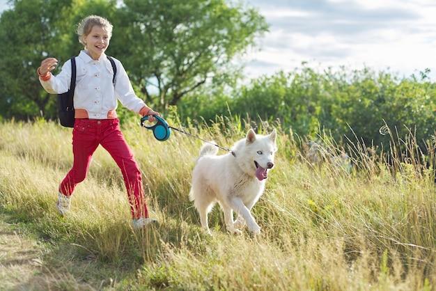 Marchez une fille avec un chien dans la nature, courez un enfant avec un animal de compagnie dans une prairie ensoleillée. mode de vie sain et actif, marcher avec un chien, amitié d'un enfant avec un animal
