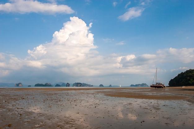 Marée basse en mer avec des rochers à l'horizon et un catamaran sans eau