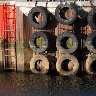 Marée marquée pneus suspendus sur un quai à côté d'une échelle à l'eau