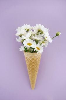 Marguerites blanches dans un cône de gaufres sur un fond lilas clair
