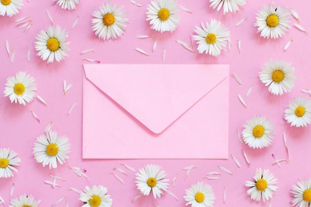 Marguerites blanches et une enveloppe sur une vue de dessus de fond rose clair