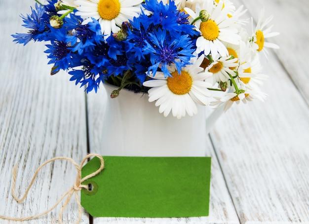 Marguerites et bleuets dans un vase
