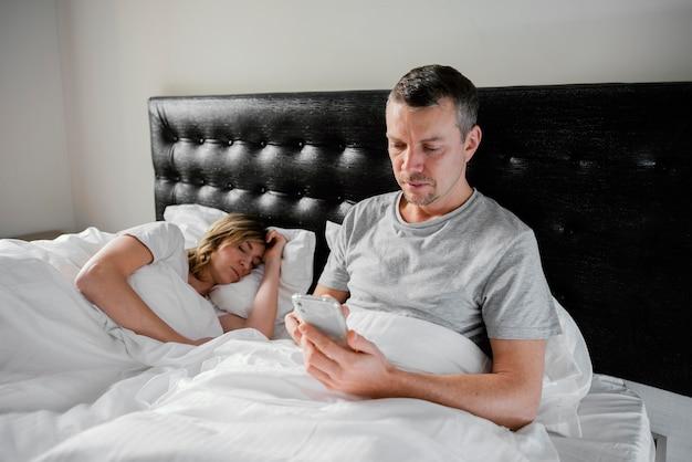 Mari à l'aide d'un mobile pendant que sa femme dort