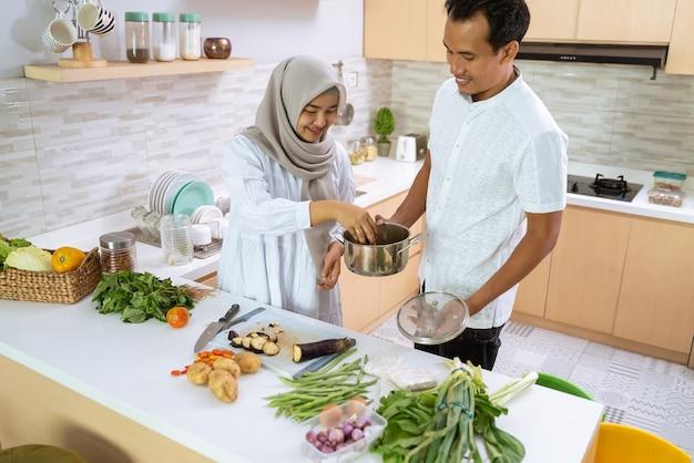 Le mari aide sa femme dans la cuisine. couple asiatique musulman prépare le dîner ensemble. jeune homme et femme romantique s'amusent à faire de la nourriture à la maison