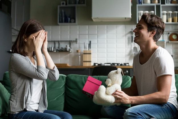 Mari aimant fermant les yeux de la femme présentant un cadeau surprise romantique