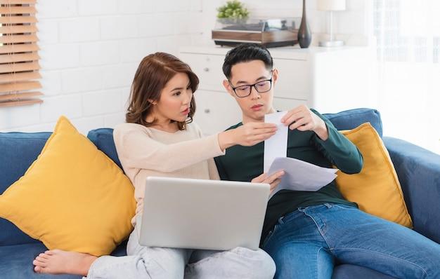 Mari asiatique sérieux vérifiant l'analyse des factures de services publics de déclaration assis ensemble à la maison.