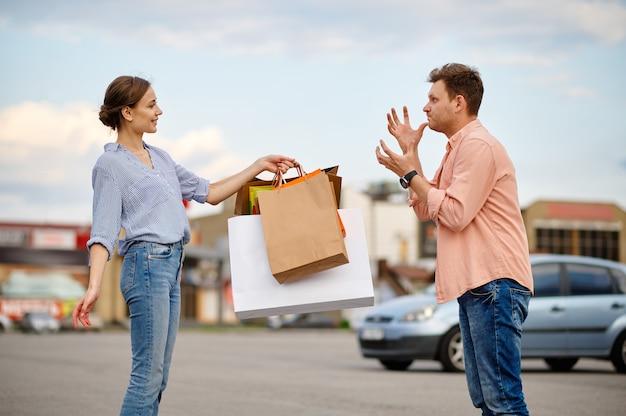 Mari en colère et femme souriante sur le parking