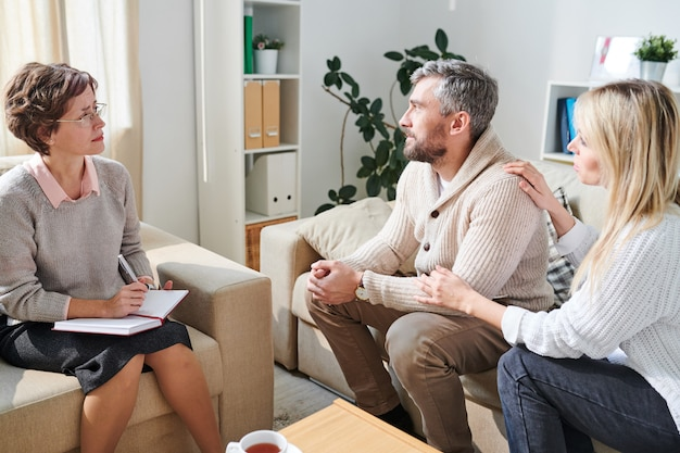 Mari en dépression visitant sa femme à un psychologue