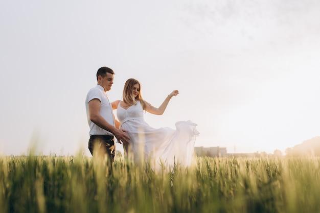 Le mari embarque le ventre de sa femme et se tient sur le terrain