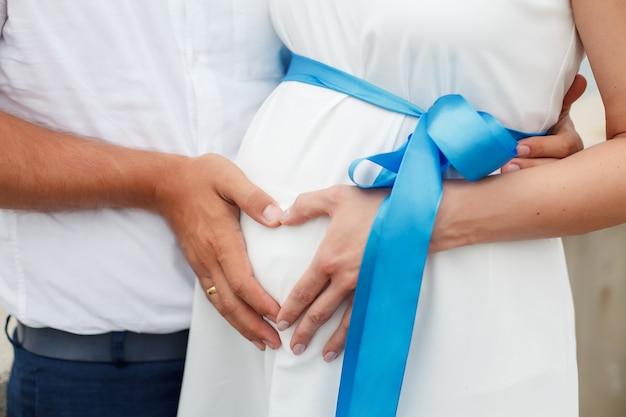 Un mari embrasse sa femme enceinte dans une robe blanche, tenant ses mains en forme de cœur sur son ventre contre la mer. un couple amoureux, attend un gros plan de bébé.