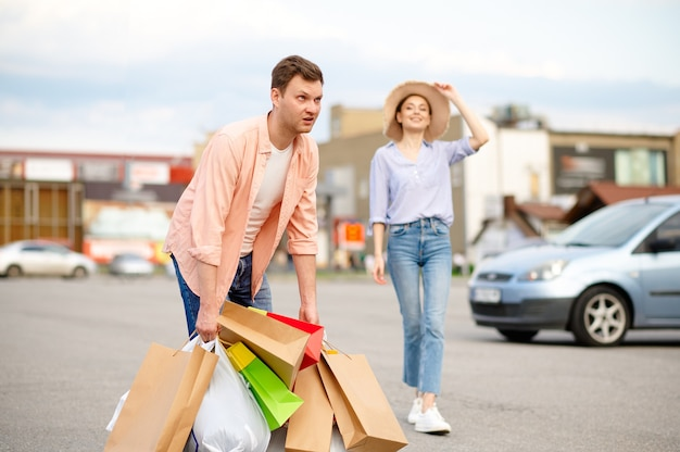 Mari fatigué portant des sacs sur le parking du supermarché. des clients heureux avec des achats près du centre commercial, des véhicules, un couple familial au marché