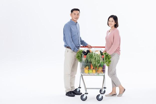 Mari et femme, acheter des légumes au supermarché