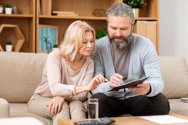Mari et femme d'âge mûr lisant les termes du contrat avant de le signer assis sur un canapé dans un bureau immobilier