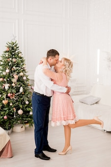 Mari et femme avec arbre de noël, le couple s'embrasse