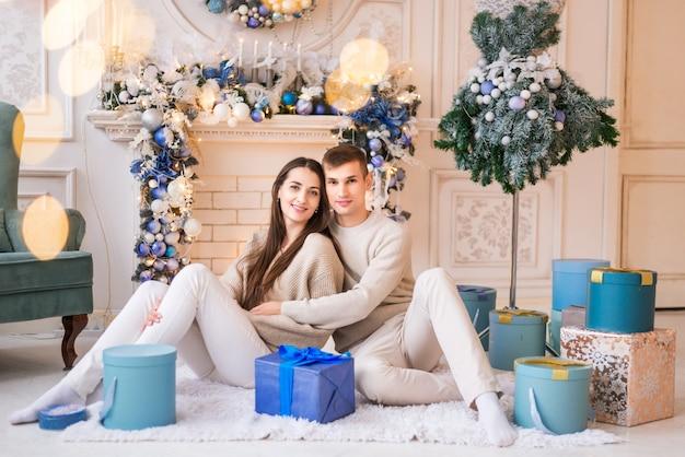 Mari et femme avec des cadeaux de noël. portrait d'un jeune couple sur fond de nouvel an