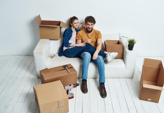 Mari femme sur le canapé dans un nouvel appartement boîtes avec des choses en mouvement