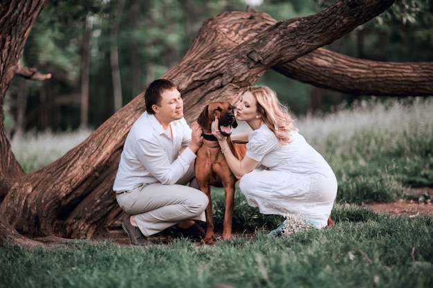 Mari et femme embrassant leur animal bien-aimé en marchant