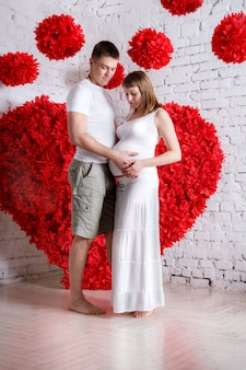 Le mari et la femme enceinte sur le coeur rouge