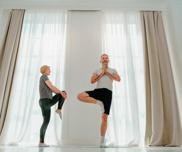 Le Mari Et La Femme Font Du Yoga Ensemble à La Maison Photo Premium