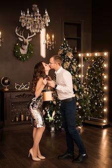 Le mari et la femme heureux se donnent des cadeaux sur le fond d'un arbre de noël