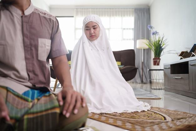 Mari et femme musulmane asiatique priant jamaah ensemble à la maison