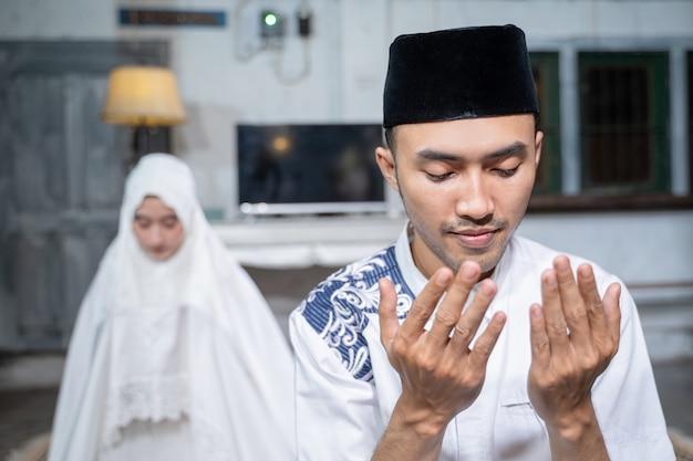 Mari et femme musulmans asiatiques priant jamaah ensemble à la maison
