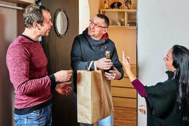 Le mari et la femme offrent un cadeau à leur ami.